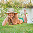 Young blond girl with a hat lying on the grass — Stock Photo #6028838