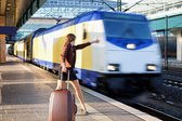 Young lady with luggage stop a train — Stock Photo