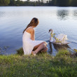 Blond woman on water background and swan — Stock Photo