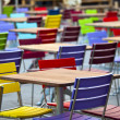 Tables and coloured chairs in a street cafe - Stock Photo