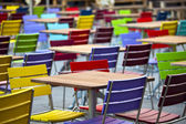 Tables and coloured chairs in a street cafe — Stock Photo