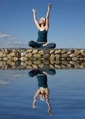 A woman doing yoga above a water — Stock Photo