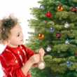 Girl dresses up a christmas-tree — Stock Photo #6050028