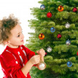 Girl dresses up a christmas-tree — Stock Photo