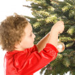 Girl hanging Christmas ornaments on the tree — Stock Photo