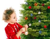 Girl dresses up a christmas-tree — Stock Photo