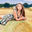 Woman sitting on hay bale — Stock Photo