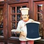 Menu board with statue of chef — Stock Photo
