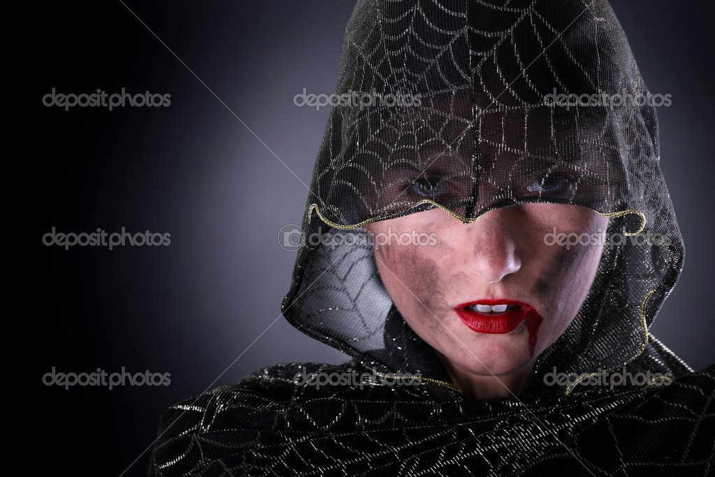 A portrait of a hooded female vampire standing against dark background  Stock Photo #6252391