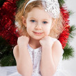 Sweetheart little girl making a wish at Christmas - Stock Photo