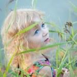 Little girl plaing alone at riverside — Stock Photo