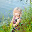 Little girl plaing alone at riverside — Stock Photo