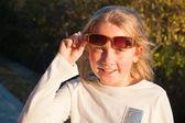 Uśmiechnięta dziewczyna sobie suglasses odkryty — Zdjęcie stockowe