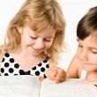 Stock Photo: Two preschooler girls reding book isolated on white