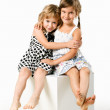 Two sisters sitting on cube isolated on white background — Stock Photo