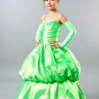 Cute little girl posing on studio neutral background in gorgeous green gown — Stock Photo