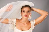 Excited bride earing a veil in studio — Stock Photo