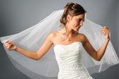 Portrait of romantic bride wearing a veil in studio — Stock Photo