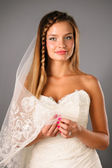 Beatiful young bride wearing wedding gown on studio neutral background — Stock Photo