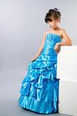 A cute girl posing in a prom dress in studio — Стоковое фото