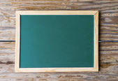 Blackboard on weathered wood — Stock Photo