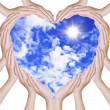 Hands make heart shape on blue sky — Stock Photo