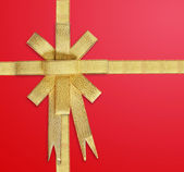 Satin Gold ribbon on red — Stock Photo