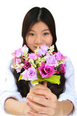 Woman smiling and showing flowers — Stock Photo