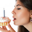 Beautiful young woman eating cupcake — Stock Photo #5961671