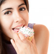 Beautiful young woman eating cupcake — Stock Photo