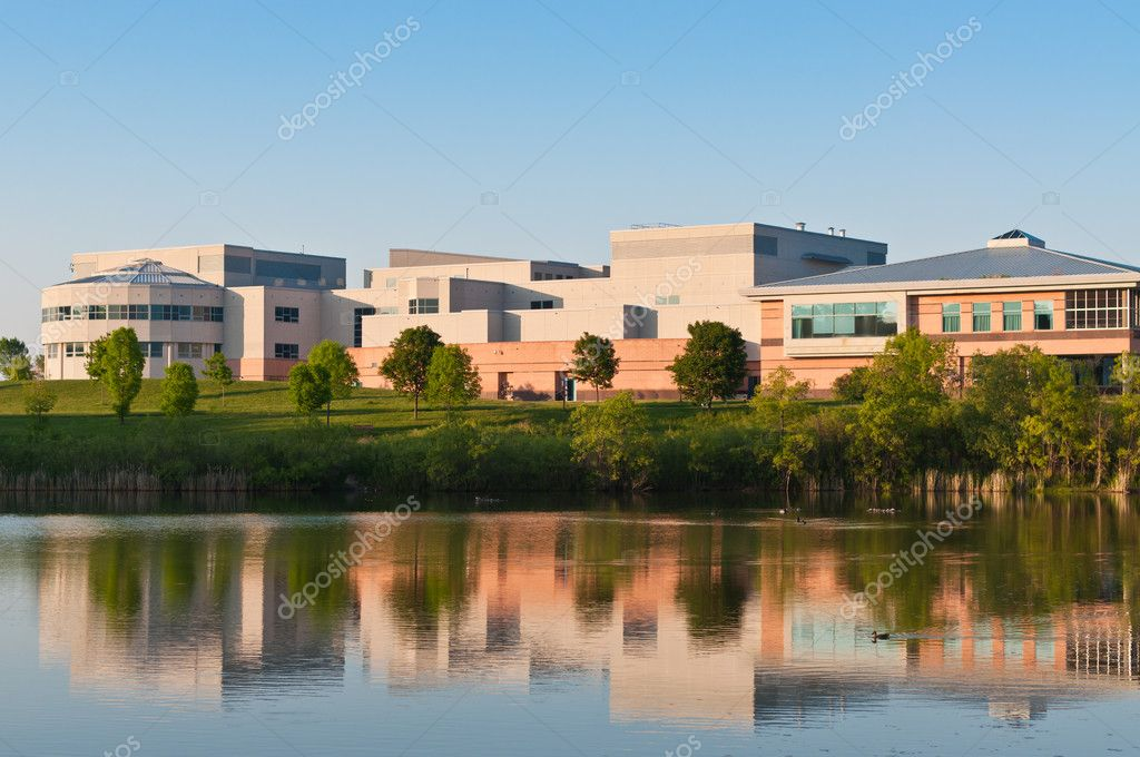 A community center building surrounded  by a park is shown reflected in the water of a large pond. — Stock Photo #5408698