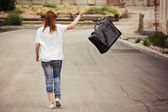 Young girl throws her suitcase walking down the street — Stock Photo