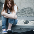 Beautiful young sad girl sitting on asphalt. Photo in cold tones - Stock Photo