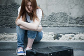 Beautiful young sad girl sitting on asphalt. Photo in cold tones — Stock Photo