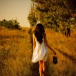 Barefoot girl in white dress with shoes in hand is on the field. — Stockfoto