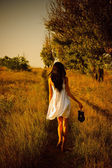 Barefoot girl in white dress with shoes in hand is on the field. — Stock Photo