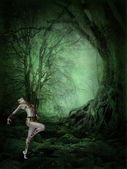 Dancing woman in a dark forest — Stock Photo