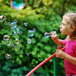 Little girl blowing interesting bubbles - Stock Photo