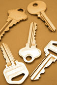 Closeup of five house keys on brown background — Stock Photo