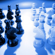 Chess pieces facing each other, blue tone - Stock Photo