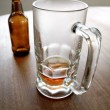 Beer bottle and empty glass on table — Stock Photo