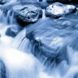 Cool blue mountain stream flowing over rocks - Stock Photo