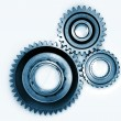 Three gears meshing together on plain background - Stock Photo