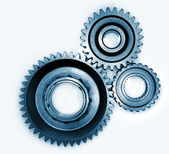 Three gears meshing together on plain background — Stock Photo