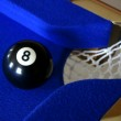 Number eight pool ball on blue pool table next to corner pocket — Stock Photo