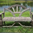 Old empty recycle wooden bench near the lake in the park — Stock Photo