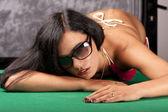 Beautiful young girl in bikini on a pool table — Stock Photo