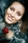 Smiling sensual girl in a smoke with a red rose — Stockfoto