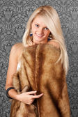 Smiling blond girl with a fur coat — Stock Photo