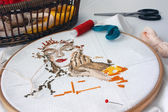 Unfinished embroidery with materials for needlework on the table — Stock Photo